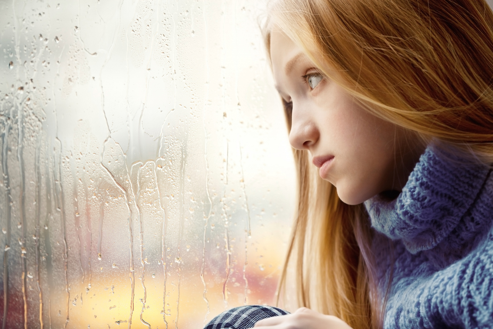 Rainy Day: Girl looking through the Window